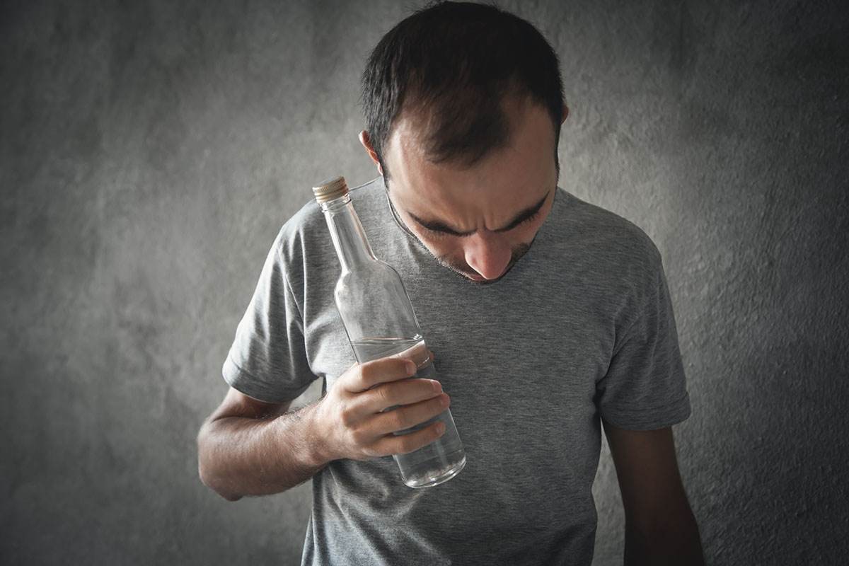 is alcoholism a disease, man struggles with bottle in his hand