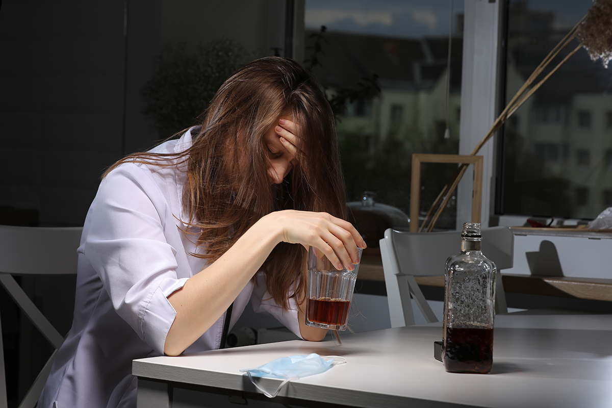 woman drinking at work in the dark to avoid Alcohol-Related Stigma